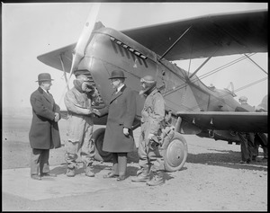 Four guys in front of a bi-plane