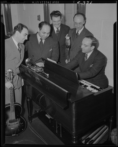Five unidentified men, possibly including Frank Bolitzeo, around a piano, with microphone, trumpet, and guitar