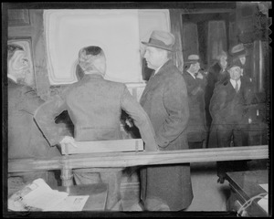 Men gathered inside of a room wearing coats, one of which is Councilman Robert Gardiner Wilson