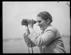 Woman with binoculars at sporting event