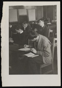 Male students writing at desks