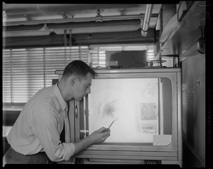 Man pointing at radar image of Hurricane Edna progress