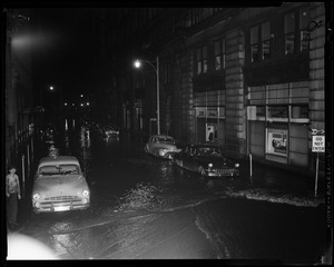Flooded street with cars parked on either side