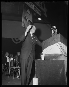 Man at podium, addressing crowd, indoors